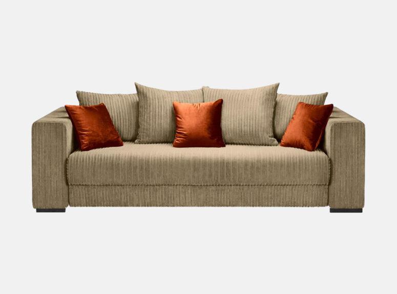 Grand - labai minkšta, didelė, erdvi rudos spalvos sofa-lova, pagaminta iš velvetinio, švelnaus, vandeniui atsparaus audinio. Sofa su spalvingomis dekoratyvinėmis oranžinėmis pagalvėlėmis.
