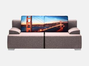 Siti pilkos spalvos sofa-lova su miesto paveiksliuku, nuimamais porankiais, patalynės dėže ir plačia miegamąja dalimi