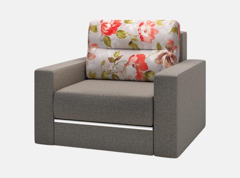 Pilkos spalvos miegamasis fotelis Prima su ryškių gėlių raštais puošta pagalve, miegamąja dalimi ir patalynės dėže.