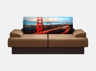 Vienvietė rudos spalvos kušetė - tachta su patalynės dėže. Kušetė spalvotu miesto ir tilto vaizdu ant pagalvės