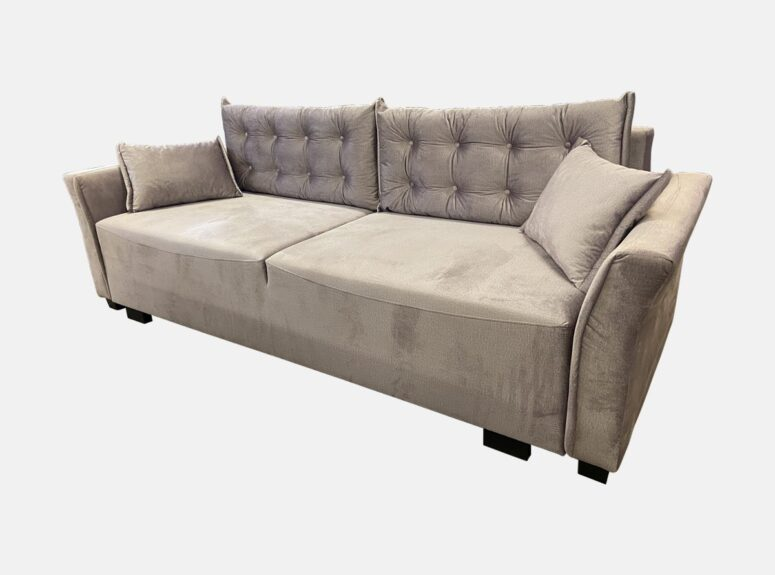 Smėlio spalvos elegantiško dizaino lietuvių gamybos sofa-lova su dygsniuotomis pagalvėmis ir mažomis dekoratyvinėmis pagalvėlėmis. Sofa su miegojimo funkcija ir patalynės dėže