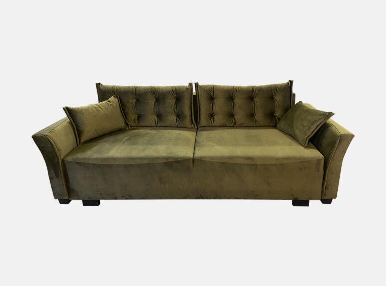 Žalios sąmanų spalvos elegantiško dizaino lietuvių gamybos sofa-lova su dygsniuotomis pagalvėmis ir mažomis dekoratyvinėmis pagalvėlėmis. Sofa su miegojimo funkcija ir patalynės dėže