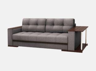 Pilkos spalvos sofa-lova nikoletti su mediniais porankiais ir staliuku. Sofa su patalynės dėže